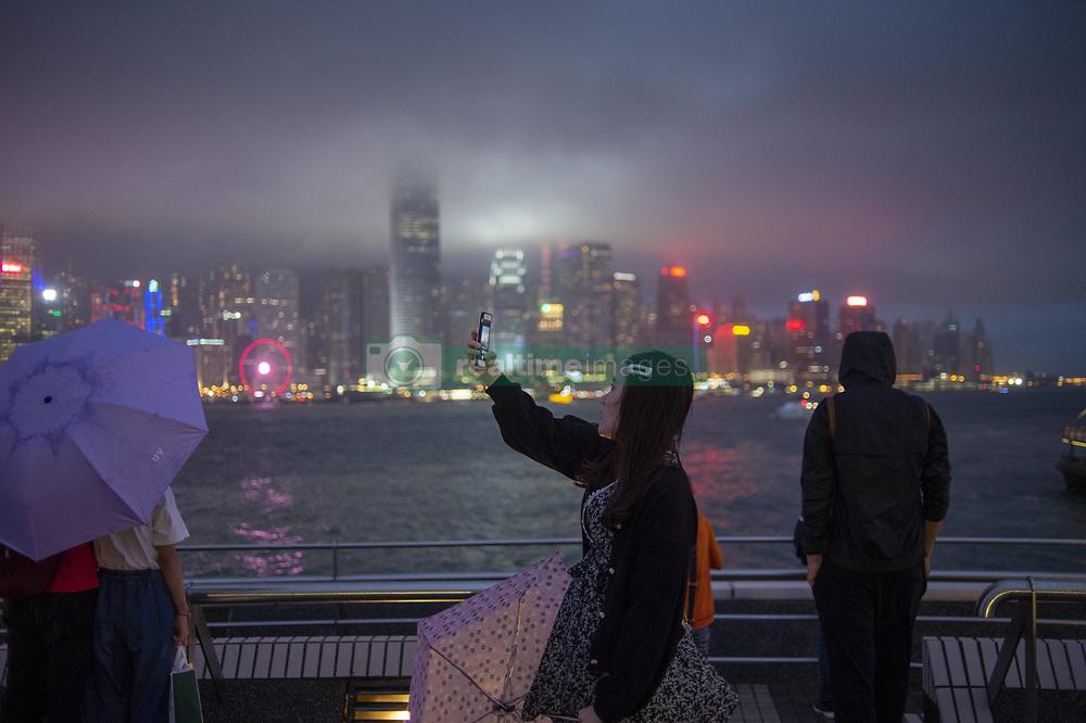 May 5, 2019 - Hong Kong, Hong Kong - A women (C) is seen taking a photo in-front of the skyline of Central District in Hong Kong, China. 5 May 2019. (Credit Image: © Vernon Yuen/NurPhoto via ZUMA Press)