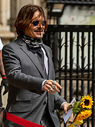 American actor Johnny Depp return to receive flowers from his supporters as he arrives at the High Court in London on Thursday, July 23, 2020 - to attend the hearing of his legal dispute with UK tabloid newspaper The Sun over allegations he assaulted his former wife Amber Heard. (VXP Photo/ Vudi Xhymshiti)