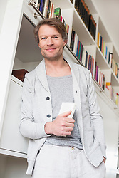 Portrait of mature man holding book, smiling