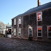The cobbled streets in Nantucket Town Centre showing the weathered Shingles used on houses built in Nantucket, Nantucket Island, Massachusetts, USA. Photo Tim Clayton