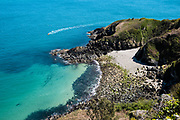 Boat speeding round the headland through calm clear water, towards Vicard Harbour, a tiny, pebbly cove on the North Coast of Jersey, CI
