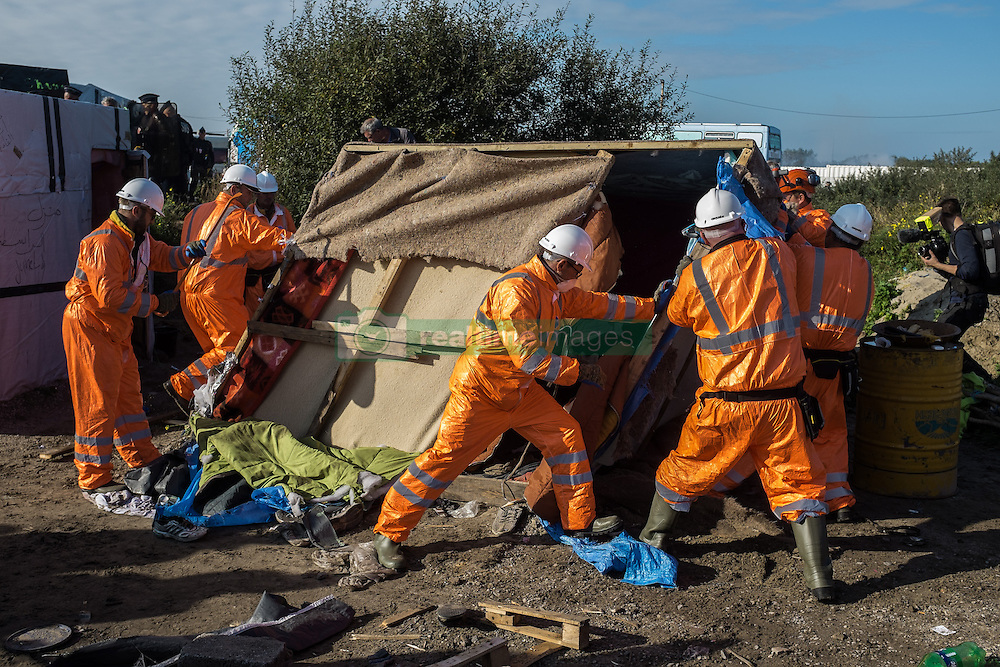 October 25, 2016 - Calais, France - Construction workers demolish during the eviction of the Calais Jungle a hut  in Calais, France, on 25 October 2016. Up to the evening, about 4,000 migrants from the Refugee camp on the coast at the English Channel were distributed to several regions in France. The police have begun to tear down the huts and tents in the camp. (Credit Image: © Markus Heine/NurPhoto via ZUMA Press)