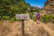 Trail sign and hiker at Lobo Canyon, Santa Rosa Island, Channel Islands National Park, California USA