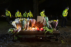 © Licensed to London News Pictures. 13/03/2021. London, UK. Police pass a bench covered with flowers, candles and placards during a vigil on Clapham Common for murder victim Sarah Everard. Metropiltan Police officer Wayne Couzens has been charged with the kidnap and murder of Sarah Everard, who went missing as she walked across Clapham Common in south London. The 33-year-old's body was found in Kent just over a week later. Photo credit: Peter Macdiarmid/LNP