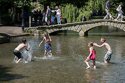 © Licensed to London News Pictures. 19/07/2016. BOURBON ON THE WATER, GLOUCESTERSHIRE, UK.  Splashing in the river Windrush  to cool off (parental permission for images). Hottest day of the year in Bourton on the Water in Gloucestershire..  Photo credit: MARK HEMSWORTH/LNP