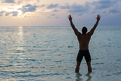 man at sunset in the ocean with his arms raised high to the sky