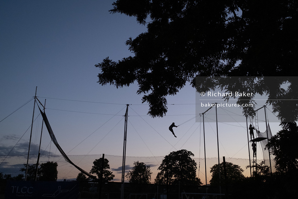 Silhouetted against evening skies, a figure performs trapeze acrobatics in Ruskin Park in Lambeth, on 29th July 2020, in London, England. TLCC Trapeze School comes to Ruskin Park each summer although during the Coronavirus pandemic, they have had to delay their presence in this south London Park.