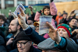 © Licensed to London News Pictures. 24/12/2018. London, UK. A customer holds money in the air as butcher Harts of Smithfield auction off cuts of meat to the public on Christmas Eve at Smithfield Market in London. Photo credit: Rob Pinney/LNP