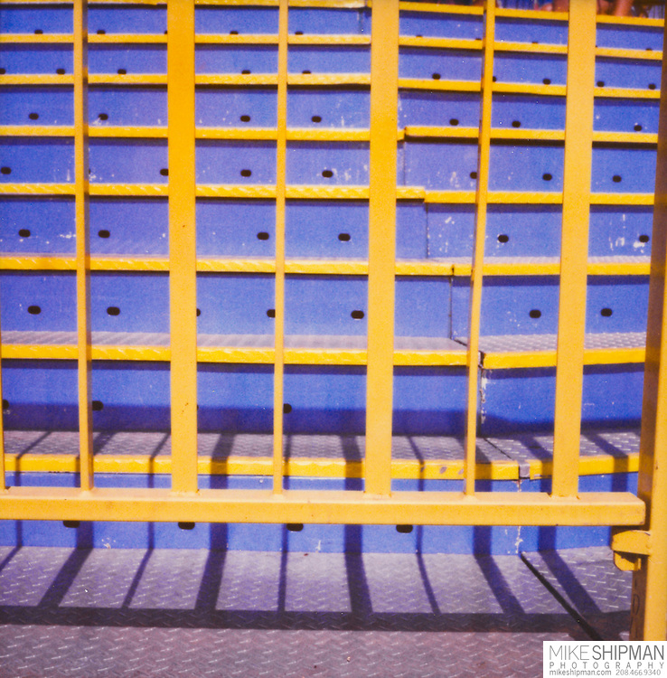 Blue steps and yellow railing bar access to a carnival ride but provide a nice graphic