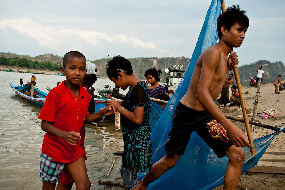 Boys carry a fishing net along the Chindwin at the village of Monywa.