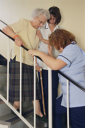 Rehabilitation assistant and physiotherapist with elderly patient practising use of stairs before discharge,