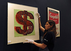 © Licensed to London News Pictures. 25/11/2011, London, UK. A Bonhams worker hangs One of Andy Warhol's Single Dollar prints valued at 15,000 - 20,000 GBP. Preview of Bonhams print sale today 25 November 2011. 'Single dollar' works by Andy Warhol feature in Bonhams' print sale which is being hung for viewing. The signed prints, estimated at between £15,000- 20,000, represent the link Warhol often made between art and money, underlined by the high prices paid for them by collectors at the time and ever since. Photo credit : Stephen Simpson/LNP