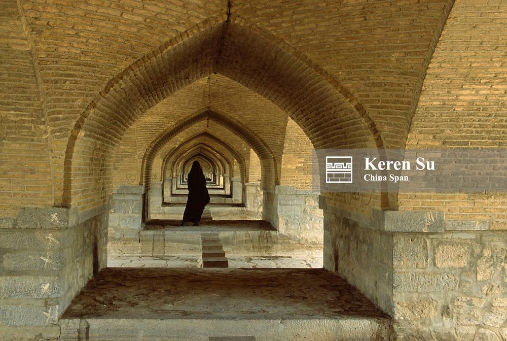 A tunnel view under the Khaju Bridge with a woman wearing black chador, Esfahan, Iran