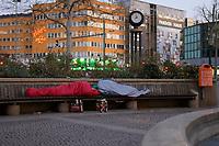 DEU, Deutschland, Germany, Berlin, 02.04.2020: Zwei Obdachlose Personen schlafen Kopf an Kopf (einer trägt jedoch einen Mundschutz) in ihren Schlafsäcken auf einer Parkbank in der Nähe des Zoologischen Gartens. Um die Ausbreitung des Coronavirus (Covid-19) zu verlangsamen, ist eigentlich in der Öffentlichkeit ein Abstand von 1,5 Metern zu anderen Personen vorgeschrieben (Abstandsregel).