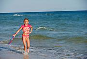 A girl carries a booogie board in the ocean in Fort Morgan, Alabama.