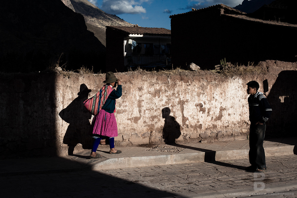 A peruvian women of the Andes walks along the street during the days last light as a boy looks on in more contemporary clothing in Pisac, Peru.
