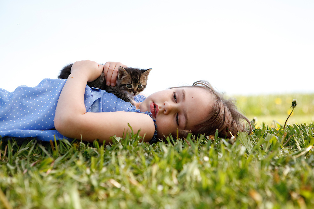 Girl in blue 4-6 years lying on grass with eyes closed and kitten on her chest