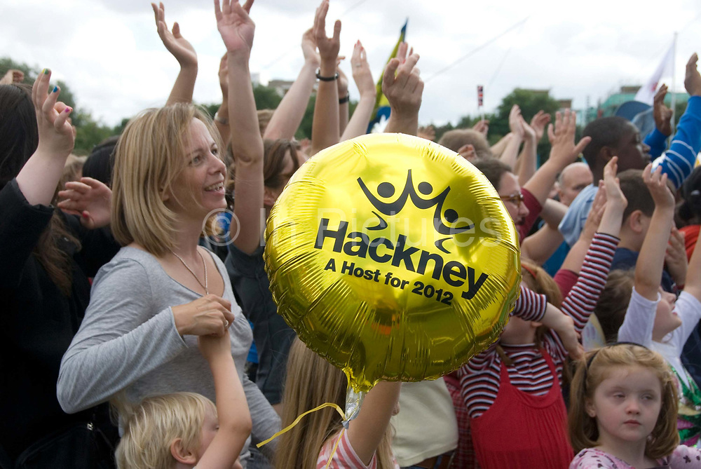 Shoreditch Park, Hackney, East London. Celebration of  the handing over of the Olympic flag  to London for 2012 Games. Children with celbratory balloon.