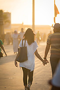Rear view of couple walking along Corniche west of Hassan II Mosque at sunset, Casablanca, Morocco