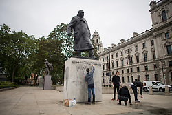 """© Licensed to London News Pictures. 08/06/2020. London, UK. Members of the public, who started at 2:30am, attempt to remove Graffiti from a statue of former British Prime Minister Winston Churchill in Parliament Square, after it was graffitied with the words """"was a racist"""" during a Black Lives Matter demonstration In central London. The death of George Floyd, who died after being restrained by a police officer In Minneapolis, Minnesota, caused widespread rioting and looting across the USA. Photo credit: Ben Cawthra/LNP"""