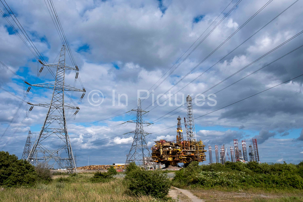 Electricity Pylons leading from Hartlepool Power Station pass the decommissioned Brent Delta Oil Rig in Able Seaton Port, Hartlepool, North East England, UK.