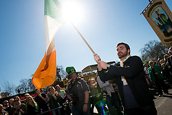 © Licensed to London News Pictures. 16/03/2014. London, UK. A flag bearer flying the national colours at the St Patrick's Day parade along Piccadilly outside Green Park. Photo credit : David Tett/LNP