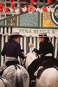 Two women on horseback conversing at the April Fair, Seville, Spain.