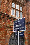 A For Sale sign stands outside the main door of River House, a building in the wool town of Kersey, being sold by the Savills and Winkworth estate agents both seen on reverse sides of the placard  that opens on to the street in on 9th July 2020, in Kersey, Suffolk, England. River House is a 15th century Elizabethan town house, on the market for £1.2m though is currently in a derelict state.  The wool trade was already present by the 13th century, steadily expanding as demand grew. By the 1470s Suffolk produced more cloth than any other county.