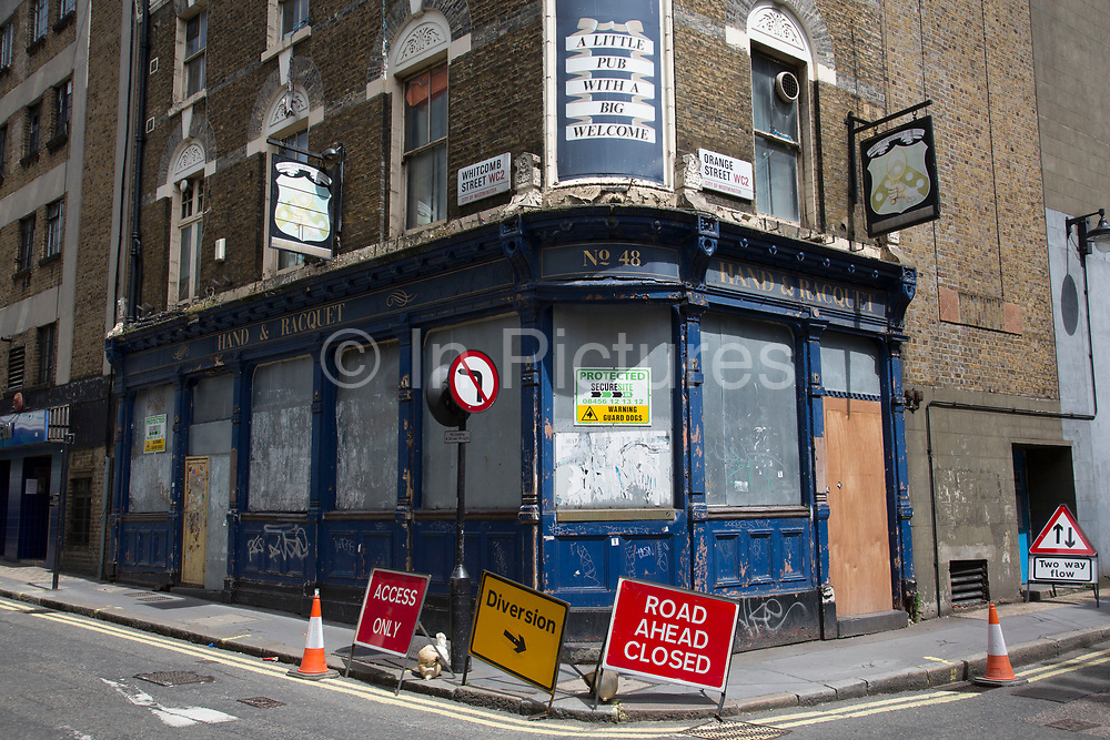 Boarded up closed down buildings are a common site now all over London and the UK. Due to the recession and other social factors, many windows are now covered. Here the Hand & Racquet pub just off Leicester Square is closed.