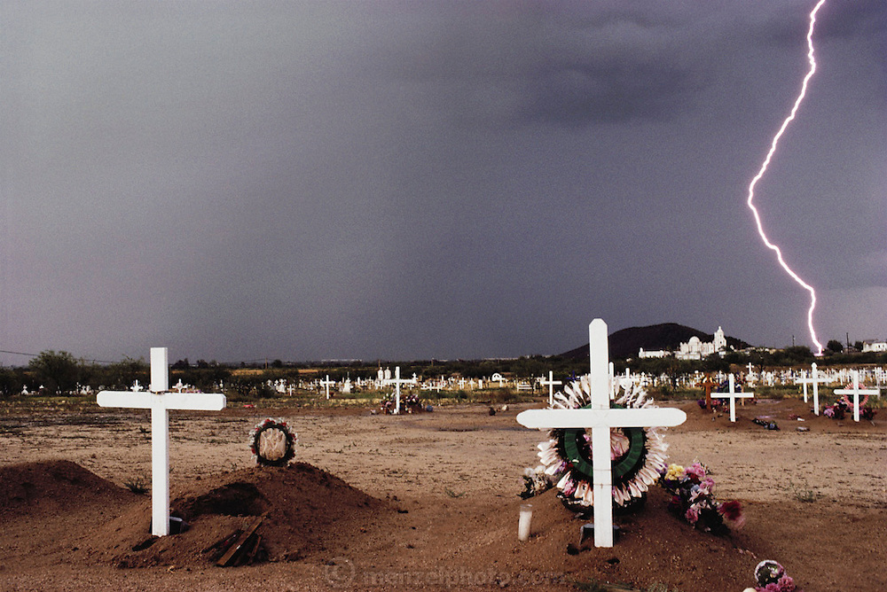 San Javier del Bac Mission. Afternoon thunderstorm with lightning stikes behind the historic Spanish mission and graveyard. 1992.