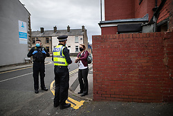 © Licensed to London News Pictures . 11/09/2020. Bolton , UK . PCs TERRY WILKINSON and TONY LOWE talk to EHO CAROLINE GREENEN after a direction order is issued to close Scott's Barber Shop in Horwich for a minimum of seven days  , with immediate effect , pending a review of the business . Police officers from Greater Manchester Police and Environmental Health Officers from Bolton Council respond to concerns of breaches of Coronavirus regulations , as stricter lockdown measures and a curfew on hospitality businesses are imposed in the borough to limit the spread of Covid-19 . Photo credit : Joel Goodman/LNP