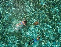 Aerial view of two people snorkeling with turtle in Panagsama Beach, Philippines.