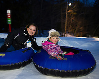 Boys and Girls Club Unit Director Mariah Hoffmann and Kendra Walter go tandem down Gunstock's tubing hill during the Boys and Girls Club Tubing Party Sunday evening.  (Karen Bobotas/for the Laconia Daily Sun)