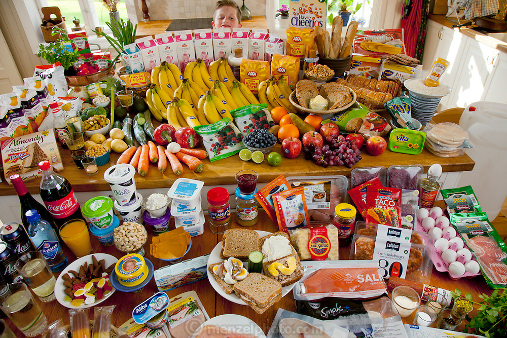 The Glad Ostensen family in Gjerdrum, Norway: Amund, 8 with their typical week's worth of food in June. Food expenditure for one week: 4265.89 Norwegian Kroner;  $731.71 USD. Model-Released.