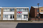 A giant union jack flag hangs from a house, the day Prince Harry and Meghan Markle get married, on the Loughborough Estate on 19th May 2018 in South London in the United Kingdom. Loughborough Estate is a large density social housing estate in Loughborough Junction, South London.