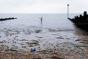 A wild swimmer walks back towards his shoes on the shingle, after a swim in the cold tidal waters of the Thames Estuary, on 26th July 2021, in Whitstable, England.