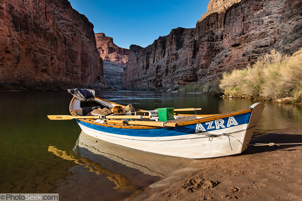 """Arizona Raft Adventures (AZRA) dory boat at Tatahatso Wash Camp (Mile 37.9) on the Colorado River in Marble Canyon in Grand Canyon National Park, Arizona, USA. Marble Canyon runs from Lees Ferry at River Mile 0 to the confluence with the Little Colorado River at Mile 62, which marks the beginning of the Grand Canyon. Although John Wesley Powell knew that no marble was found here when he named Marble Canyon, he thought the polished limestone looked like marble. In his words, """"The limestone of the canyon is often polished, and makes a beautiful marble. Sometimes the rocks are of many colors – white, gray, pink, and purple, with saffron tints."""" For this photo's licensing options, please inquire at PhotoSeek.com. ."""