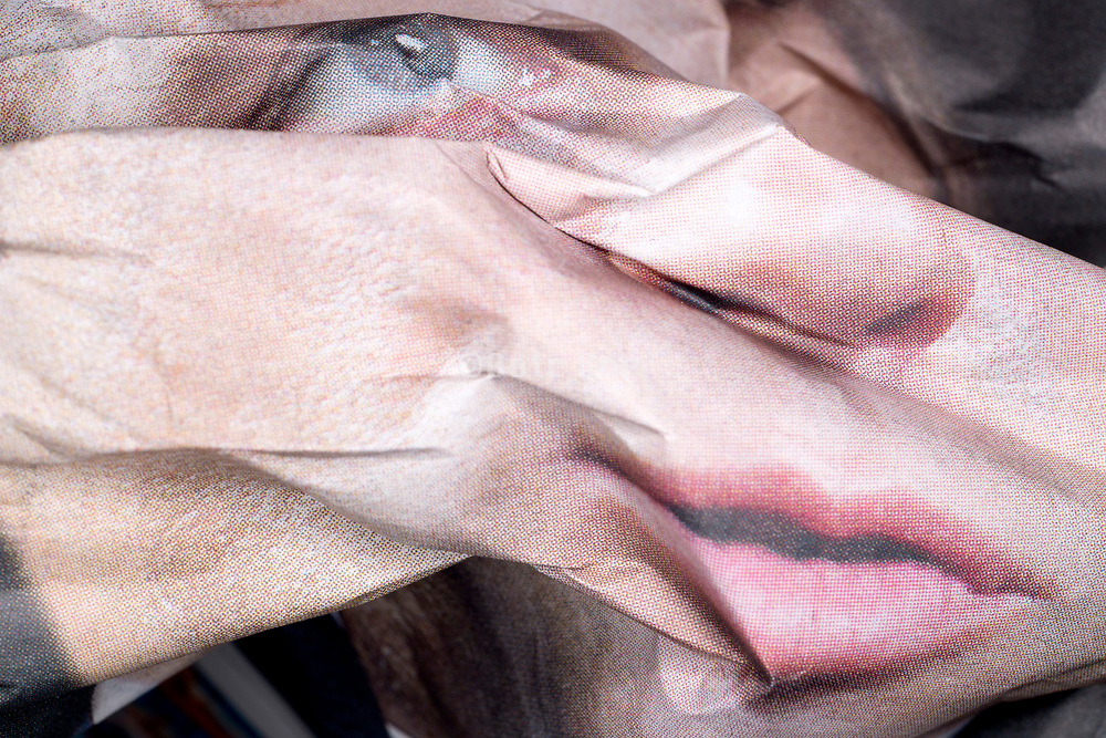 crumpled newspaper print with close up of a face