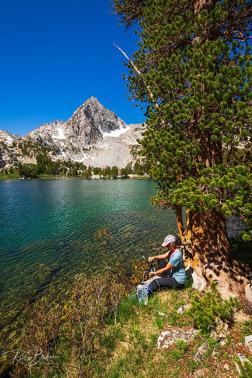 Hiker purifying water on the shore of Treasure Lake, John Muir Wilderness, Sierra Nevada Mountains, California USA