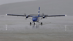 Barra Airport is a short-runway airport situated in the wide shallow bay of Traigh Mhòr at the north tip of the island of Barra in the Outer Hebrides, Scotland. Barra is now the only beach airport anywhere in the world to be used for scheduled airline services. Loganair Twin Otter landing in heavy rain. (c) Stephen Lawson   Edinburgh Elite media