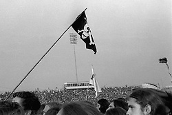 Bleachers, Crowd and Flags at the Grateful Dead Concert at Dillon Stadium on 31 July 1974. B&W Original Film Scan. Photograph taken with a Hasselblad Camera with Tri-X film. View of the Stadium and Wall of Sound in distance.