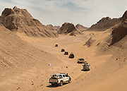 The expedition 4 x 4 cars getting deeper into the heart of the Lut desert, following Yardangs, sharp irregular ridges of sand lying in the direction of the prevailing wind in exposed desert regions, formed by the wind erosion of adjacent material which is less resistant.