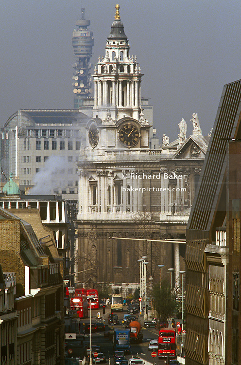 An aerial cityscape of polluting street traffic below St Paul's Cathedral during the early-1990s. Looking down from a high viewpoint we see London traffic and polluted streets below with the corner of St Paul's Cathedral before its stonework was cleaned, its stained surfaces removed after centuries of grime and poor air quality. Red Routemaster buses drive from Ludgate Hill towards Cannon Street into the City, London's London's financial district.