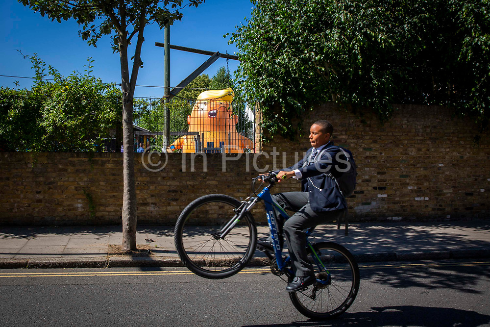 A teenager pulls a wheelie on his bicycle unaware of the six metre high inflatable Trump Baby during his first London outing inside the disused North London playground, Islington, London, United Kingdom. 26th June 2018. The plan, is to fly him above Parliament Square in Westminster when the real Trump, president of the United States arrives in the United Kingdom on the 13th of July 2018.