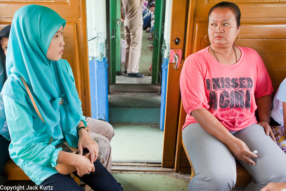 """Sept. 26, 2009 -- YALA, THAILAND: Muslim and Buddhist Thais sit opposite each other on a train going from Pattani to Yala in southern Thailand. Thailand's three southern most provinces; Yala, Pattani and Narathiwat are often called """"restive"""" and a decades long Muslim insurgency has gained traction recently. Nearly 4,000 people have been killed since 2004. The three southern provinces are under emergency control and there are more than 60,000 Thai military, police and paramilitary militia forces trying to keep the peace battling insurgents who favor car bombs and assassination.  Photo by Jack Kurtz / ZUMA Press"""