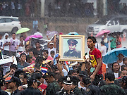 23 JUNE 2016 - MAHACHAI, SAMUT SAKHON, THAILAND: People hold up a photo of Gen Aung San while they wait in a driving rainstorm to see his daughter, Aung San Suu Kyi, after her visit to the Burmese community in Samut Sakhon, a province south of Bangkok. Tens of thousands of Burmese migrant workers, most employed in the Thai fishing industry, live in Samut Sakhon. Aung San Suu Kyi, the Foreign Minister and State Counsellor for the government of Myanmar (a role similar to that of Prime Minister or a head of government), is on a state visit to Thailand. Even though she and her party won the 2015 elections by a landslide, she is constitutionally prohibited from becoming the President due to a clause in the constitution as her late husband and children are foreign citizens        PHOTO BY JACK KURTZ