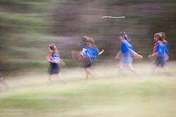 Guatemalan girl scouts running through grass, Antigua, Guatemala