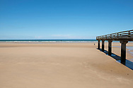A pier extends out over Omaha Beach in Vierville-sur-Mer, Normandy, France. This was one of the Allied landing beaches on D-Day in 1994. An unidentifiable person walks in the distance.