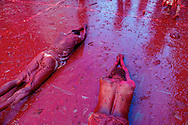 Men lying on the floor full of mud-of-color, in order to show respect to the Gods.