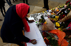 © Licensed to London News Pictures.06/12/2013. London, UK. A woman writes a farewell message to Nelson Mandela at the statue of Nelson Mandela in Parliament Square, London to pay tribute to late former South African president Nelson Mandela following his death in Johannesburg.Photo credit : Peter Kollanyi/LNP